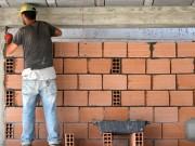 Construction d'un mur par un maçon